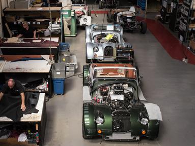 Pekerja mencetak kulit yang akan dibuat sebagai jok mobil klasik sport di pabrik mobil Morgan Motor Company di Malvern, Birmingham, Inggris (13/8/2019). Morgan Motor Company didirikan pada tahun 1909 oleh HFS Morga. (AFP Photo/Oli Scarff)
