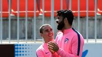 Penyerang Atletico Madrid, Antoine Griezmann dan Diego Costa bercanda saat sesi latihan di Ciudad Deportiva Wanda di Madrid (2/5). Pada leg pertama Atletico Madrid bermain imbang 1-1 atas Arsenal di Emirates Stadium. (AFP Photo/Pierre-Philippe Marcou)