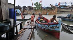 Nelayan beraktivitas saat banjir rob menggenangi permukiman Muara Angke, Jakarta, Selasa (22/1). Banjir air laut pasang atau Rob yang kembali melanda kawasan itu sejak 6 hari lalu membuat aktivitas warga sekitar terganggu. (Merdeka.com/Iqbal S. Nugroho)