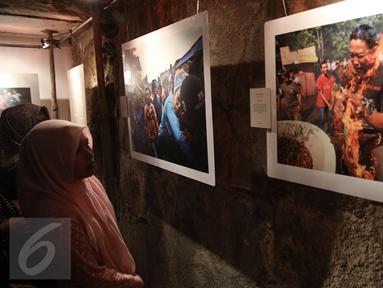 Pengunjung mengamati foto saat pameran foto Anugerah Pewarta Foto Indonesia (APFI) ke-VI di Gedung Bandung, Sabtu (9/4). APFI 2016 memamerkan 25 foto tunggal dan tiga foto seri terbaik sepanjang tahun 2015. (Liputan6.com/Faizal Fanani)