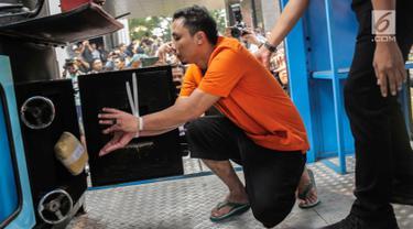 Tersangka memasukkan barang bukti narkoba ke dalam mesin insimilator saat pemusnahan di Bareskrim Mabes Polri, Jakarta, Selasa (9/7/2019). Bareskrim Polri memusnahkan 177,5 Kg sabu dan 30 ribu butir ekstasi yang disita dari jaringan Malaysia-Indonesia. (Liputan6.com/Fazail Fanani)