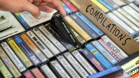 Giorgio Carbone, salah satu pendiri Mars Tapes memilih kaset di tokonya di Manchester, Inggris, 4 September 2021. Toko yang terselip pada sudut lantai atas pasar dalam ruangan di Manchester ini menjadi toko terakhir di Inggris yang didedikasikan untuk menjual kaset. (PAUL ELLIS/AFP)