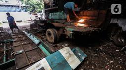 Seorang pekerja membelah Koperasi Angkutan Jakarta (Kopaja) yang akan diremajakan di kawasan Meruya, Jakarta Barat, Rabu (27/1/2021). Kopaja yang tak lagi digunakan tersebut dihancurkan untuk dijual secara kiloan ke penjual besi tua. (Liputan6.com/Johan Tallo)