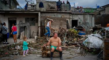 Seorang pria beristirahat di batang pohon yang terhantam tornado saat membersihkan puing-puing dirumahnya di Regla, Kuba (28/1). Tornado dan hujan deras menghantam Bagian timur ibukota Kuba. (AP Photo/Ramon Espinosa)