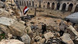 Anggota pasukan Presiden Suriah Bashar al-Assad, mengibarkan bendera Suriah di antara puing bangunan yang hancur karena gempuran senjata selama perang saudara berlangsung, di kompleks Masjid Umayyad, Aleppo, 13 Desember 2016. (REUTERS/Omar Sanadiki)