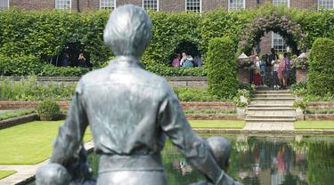Anggota masyarakat melihat patung Dianam di Taman Sunken di Istana Kensington, London, Jumat (2/7/2021). Peresmian patung ini menandai ulang tahun ke-60 tahun Putri Diana.  (Jonathan Brady/Pool Photo via AP)