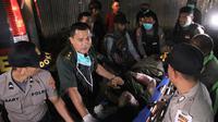 Polisi dan tim medis membawa seorang anggota Brimob yang tertembak saat kontak tembak dengan Kelompok Kriminal Bersenjata (KKB) di Nduga, Papua, Rabu (5/12). Korban saat ini mendapat perawatan medis di sebuah rumah sakit di Wamena. (ANYONG/AFP)