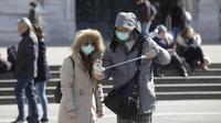 Suami istri bersiap selfie di kota Duomo, Milan, Italia, Kamis (27/2/2020). Kementerian Kesehatan Italia, hingga Rabu 4 Maret, mencatat ada 3.089 orang yang terinfeksi Virus Corona COVID-19. Rinciannya, 2.706 kasus positif, 107 orang meninggal dunia, dan 276 orang sembuh. (AP Photo/Luca Bruno)