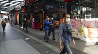 Para pejalan kaki memakai masker saat berjalan di distrik perbelanjaan di Kuala Lumpur, Malaysia, Kamis (14/1/2021). Otoritas Malaysia memperketat pembatasan pergerakan untuk mencoba menghentikan penyebaran virus corona COVID-19. (AP Photo/Vincent Thian)