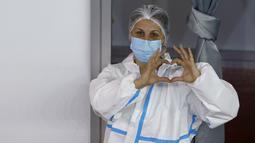 Pekerja medis mengenakan APD saat orang-orang menunggu menerima vaksin COVID-19, di pusat vaksinasi darurat Belgrade Fair, di Beograd, Serbia, Senin (25/1/2021). Serbia adalah negara Eropa pertama yang menerima vaksin COVID-19 Sinopharm China untuk program inokulasi massal (AP Photo/Darko Vojinovic)