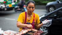 Seorang wanita memasak sate di gerobaknya di samping jalan di Bangkok, Thailand (20/9). Kota Bangkok, terkenal sebagai salah satu street food capital alias kota yang identik dengan makanan pinggir jalan. (AFP Photo/Jewel Samad)