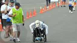 Raechana Syafei (45 tahun) memacu kursi roda dan sampai di garis finish dengan waktu 2 jam 15 menit dengan jarak lari 10 km. (Liputan6.com/Andrian M. Tunay)