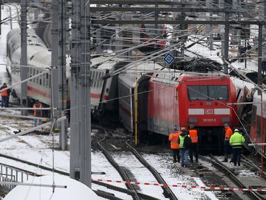 Regu penyelamat berdiri dekat dua rangkaian kereta penumpang yang terlibat tabrakan dekat stasiun di Niklasdorf, Austria, Senin (12/2). Tabrakan kereta itu menyebabkan satu orang tewas dan 22 lainnya terluka, tiga di antaranya anak-anak. (AP/Ronald Zak)