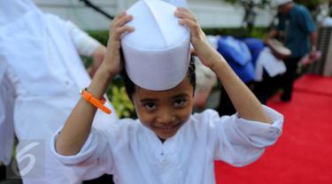Seorang anak yatim terlihat tersenyum usai mengambil air wudhu, Jakarta, Kamis (18/6/2015). Jokowi mengundang 400 anak yatim dari 12 panti asuhan yang ada di Jabodetabek untuk berbuka puasa bersama di Isatana Negara (Liputan6.com/Faizal Fanani)