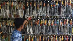 Seorang pria memilih pisau yang dipasangkan rantai untuk ritual pencambukan diri selama ritual berkabung Ashura di sebuah toko di Lahore, Pakistan (18/9). Umat Syiah Pakistan akan memperingati hari Ashura pada 21 September. (AFP Photo/Arif Ali)