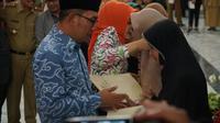 Gubernur Jawa Barat Ridwan Kamil membeirkan penghargaan dan santunan secara simbolis kepada beberapa beberapa ahli waris dari 49 petugas yang gugur di Aula Gedung Sate, Selasa (23/4/2019). (Huyogo Simbolon)