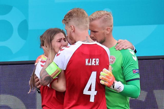 Pemain Denmark, Kasper Schmeichel (kanan) dan Simon Kjaer (tengah) menghibur Sabrina Kvist Jensen, kekasih gelandang Denmark, Christian Eriksen setelah pingsan di lapangan pada laga Denmark vs Finlandia di Grup B Euro 2020 di Parken Stadium, Copenhagen, Sabtu (12/6/2021). (WOLFGANG RATTAY/AFP/POOL)