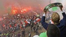 Pemain dan suporter bersorak merayakan pesta juara Liga Belanda di Rotterdam (15/5). Bagi Feyenoord, ini adalah gelar liga pertama dalam kurun waktu 18 tahun terakhir atau yang ke-15 sepanjang sejarah klub. (AFP Photo/ANP/Olaf Kraak/Netherlands Out)