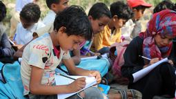 Anak-anak mengikuti kelas terbuka di desa al-Kashar Yaman barat daya, provinsi Taez (16/9/2019). Kelas-kelas diberikan di lapangan di luar sekolah yang sedang dibangun tetapi tidak pernah selesai ketika dana dihentikan karena perang yang pecah di Yaman pada tahun 2015. (AFP Photo/Ahmad Al-Basha)