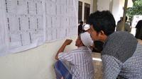 sejumlah warga di Bangkalan mengamati daftar caleg sebelum nyoblos ke TPS