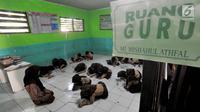 Sejumlah siswa belajar di lantai kelas di Madrasah Ibtidaiyah (MI) Misbahul Athfal, Kampung Cileuleuy, Desa Cibentang, Kecamatan Ciseeng, Bogor, Kamis (8/8/2019). Mirisnya lagi, kegiatan belajar di satu ruangan dengan guru hanya diskat menggunakan triplek. (merdeka.com/Arie Basuki)