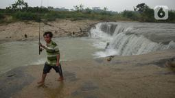Warga membawa alat pancing usai memancing ikan di sungai Cileungsi, Pasir Mukti, Jawa Barat, Sabtu (29/5/2021).  Mencari ikan dengan alat pancing seadanya merupakan cara warga di sekitar Sungai Cileungsi untuk mengisi kekosongan waktu. (merdeka.com/Imam Buhori)