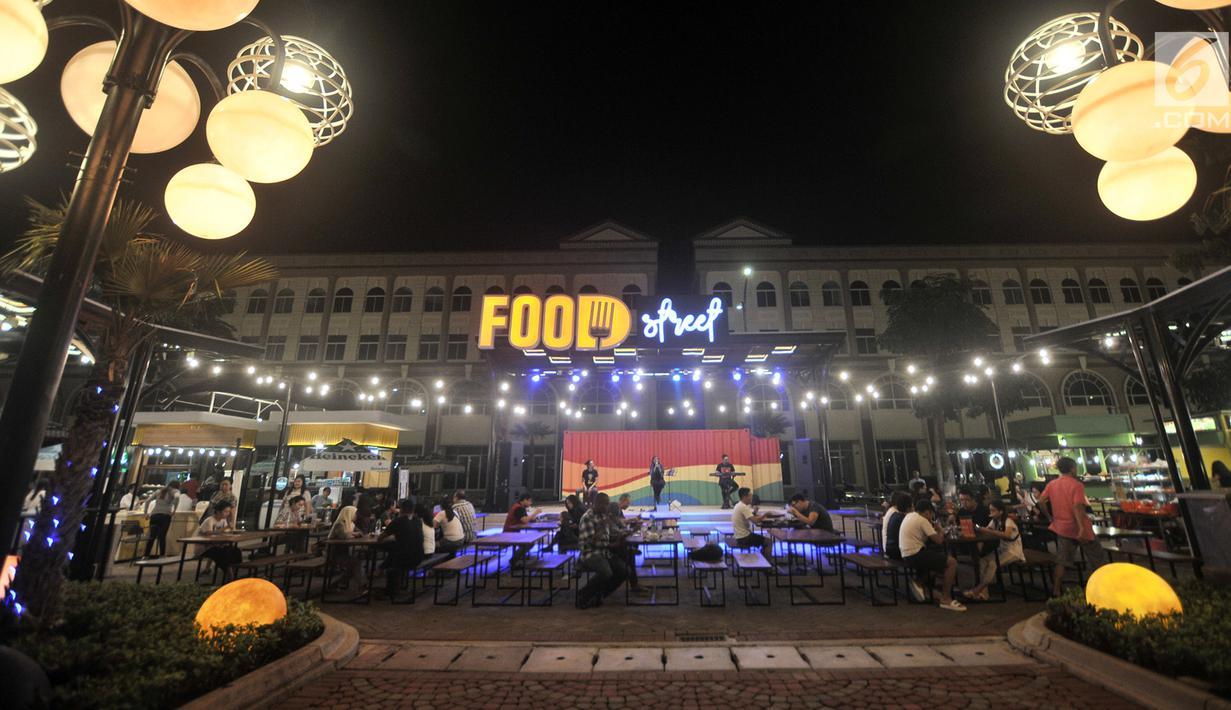 Pengunjung menikmati makanan di area Food Street di Pulau D reklamasi atau Pantai Maju, Jakarta, Selasa (29/1). Ada lebih dari 30 kios di Food Street Pantai Maju yang beroperasi setiap hari pukul 17.00-24.00 WIB tersebut. (Merdeka.com/Iqbal S. Nugroho)