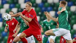 Penyerang Norwegia, Erling Braut Haaland, berebut bola dengan bek Irlandia Utara, Daniel Ballard, pada laga UEFA Nations League di Windsor Park, Selasa (8/9/2020) dini hari WIB. Norwegia menang telak 5-1 atas Irlandia Utara. (AFP/Paul Faith)