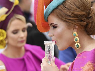 Seorang wanita minum sebelum pertandingan pacuan kuda Piala Melbourne di Melbourne (5/11/2019). Para wanita tampil cantik dan modis dengan hiasan kepala yang mereka gunakan selama menyaksikan balap kuda di Melbourne Cup.  (AFP Photo/William West)