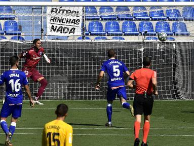 Pemain Barcelona Luis Suarez (kanan) mencetak gol ke gawang Alaves pada pertandingan La Liga di Stadion Mendizorroza, Vitoria, Spanyol, Minggu (19/7/2020). Barcelona menang 5-0. (AP Photo/Alvaro Barrientos)