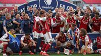 Striker Arsenal, Pierre-Emerick Aubameyang (tengah) menjatuhkan trofi saat merayakan gelar juara Piala FA usai mengalahkan Chelsea pada pertandingan final Piala FA di stadion Wembley, Minggu (2/8/2020).  Aubameyang terlihat kaget sambil memegang kepalanya saat trofi terjatuh. (Adam Davy/Pool via AP)