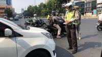 Polisi menindak pelanggar aturan ganjil genap di Jalan Hayam Wuruk dan Jalan Gajah Mada, Jakarta Barat. (Liputan6.com/Ratu Annisa)