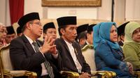 Presiden Jokowi (tengah) didampingi Ibu Negara, Iriana Jokowi (kanan) dan Menag Lukman Hakim ketika menghadiri acara Peringatan Isra Miraj Nabi Muhammad SAW Tahun 1436 H/2015 M di Istana Negara, Jakarta, Jumat (15/5) malam. (Liputan6.com/Faizal Fanani)