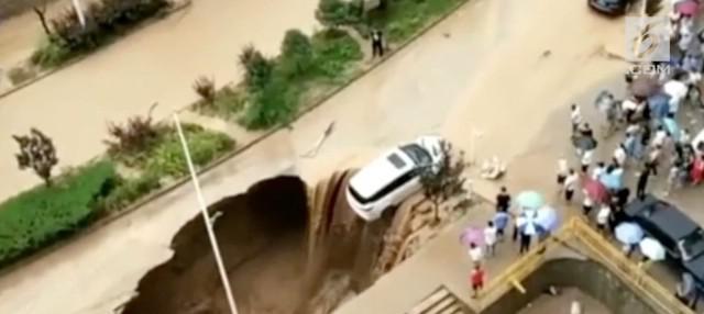Sebuah mobil terseret arus banjir bandang hingga nyaris masuk ke dalam sinkhole di China. Warga bekerja sama menyelamatkan mobil tersebut.