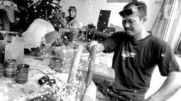 Penyandang disabilitas Catur Bambang (45) menyelesaikan pembuatan sepeda motor roda tiga di bengkelnya, Jalan Wijaya Kusuma, Ciputat Timur, Tangerang Selatan, Banten, Selasa (5/11/2019). Catur membuat sepeda motor roda tiga untuk memudahkan mobilitas penyandang disabilitas. (merdeka.com/Arie Basuki)