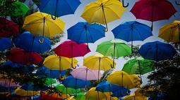 Payung warna-warni bagian dari instalasi seni Umbrella Sky menggantung di atas Coral Gables, Florida, 16 Juli 2018. Selain menciptakan pemandangan indah, payung-payung tersebut dapat melindungi orang-orang dari sengatan sinar matahari. (AP/Brynn Anderson)