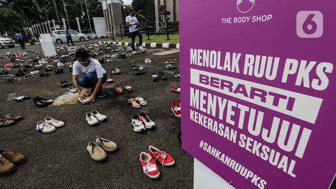 Pegiat komnas perempuan merapikan sepatu saat aksi diam 500 Langkah Awal Sahkan RUU PKS di depan gedung DPR, Jakarta, Rabu (25/11/2020). Dalam aksinya mereka menyusun sepatu sebagai simbol