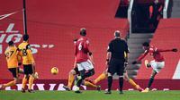 Striker Manchester United, Marcus Rashford (kanan) melepaskan tendangan yang berbuah gol ke gawang Wolverhampton Wanderers dalam laga lanjutan Liga Inggris 2020/21 pekan ke-16 di Old Trafford, Selasa (29/12/2020). Manchester United menang 1-0 atas Wolverhampton. (AFP/Laurence Griffiths/Pool)