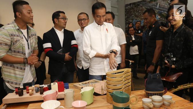 Calon Presiden Nomor Urut 01 Joko Widodo didampingi Gubernur Jawa Barat Ridwan Kamil (kedua kiri) mencoba memakai jam yang dipamerkan sebelum berdiskusi dengan masyarakat kreatif Bandung di Simpul Space, Bandung, Sabtu (10/11). (Liputan6.com/Angga Yuniar)