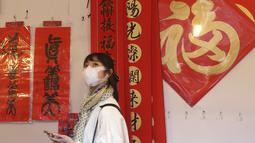 Seorang wanita memakai masker untuk mencegah penyebaran virus corona berjalan melalui lorong-lorong yang dihias dekorasi Imlek di sepanjang pasar Jalan Dihua di Taipei, Taiwan, Rabu (10/2/2021).  (AP Photo/Chiang Ying-ying)