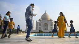Sejumlah wisatawan mengunjungi Taj Mahal setelah dibuka kembali untuk pengunjung di Agra, Rabu (16/6/2021). Taj Mahal, yang terkenal sebagai ikonik India telah dibuka kembali untuk umum, ketika negara itu mulai melonggarkan pembatasan Covid-19. (Money SHARMA/AFP)