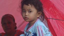 Seorang gadis sedang sarapan di kamp sementara setelah gempa berkekuatan 6,2 di Mamuju,  Senin (18/1/2021). Pengungsi masih mengharapkan bantuan berupa bahan pangan dan obat-obatan karena rata-rata para pengungsi merupakan anak-anak, yang rawan terserang penyakit. (AFP/Adek Berry)