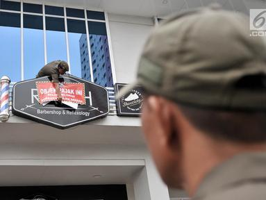 Petugas Satpol PP memasang stiker tunggak pajak di salah satu kios Green Pramuka Square Mall, Jakarta, Rabu (7/11). Kegiatan ini dilakukan guna memberi sanksi sosial ke pemilik untuk segera menyelesaikan penunggakan pajak. (Merdeka.com/Iqbal S. Nugroho)