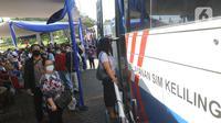 Warga mengantre untuk pembuatan dan memperpanjang SIM di mobil layanan SIM Keliling Masjid At-Tin TMII, Jakarta Timur, Kamis (4/6/2020). Direktorat Lalu Lintas Polda Metro Jaya mengoperasikan kembali layanan mobil SIM Keliling untuk mengantisipasi antrean pemohon. (Liputan6.com/Herman Zakharia)
