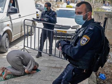 Dua anggota pasukan keamanan Israel berjaga saat seorang jemaah Palestina melaksanakan salat Jumat selama bulan suci Ramadan di tengah krisis pandemi coronavirus di luar kompleks masjid al-Aqsa di Kota Tua Yerusalem (15/5/2020). (AFP/Ahmad Gharabli)