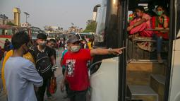 Seorang sopir menunjukkan bus kepada penumpang untuk kembali ke desa mereka sehari sebelum lockdown di Kathmandu, Rabu (28/4/2021). Puluhan ribu orang meninggalkan ibu kota Nepal sehari menjelang lockdown selama 15 hari yang diberlakukan karena melonjaknya kasus COVID-19 (AP Photo/Niranjan Shrestha)