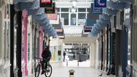Seorang pria bersepeda melewati deretan toko yang tutup di Leeds, Inggris, pada 5 November 2020. Inggris memasuki karantina wilayah (lockdown) selama sebulan mulai Kamis (5/11) untuk meredam merebaknya kembali penularan virus corona. (Xinhua/Jon Super)