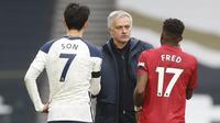 Pelatih Tottenham Hotspur, Jose Mourinho (tengah)  berbicara dengan Son Heung-min (kiri) dan Fred selama pertandingan pertandingan lanjutan Liga Inggris di Stadion Tottenham Hotspur di London, Senin (12/4/2021).  MU menang atas Tottenham 3-1. (Matthew Childs/Pool via AP)