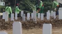 Petugas melakukan perawatan makam jenazah protokol Covid-19 di TPU Srengseng Sawah Dua, Jakarta, Kamis (18/3/2021). Dinkes DKI Jakarta mencatat penambahan kasus kematian akibat Covid-19 pada Maret 2021 berada diatas 40 atau meningkat dari 1,6 menjadi 1,7