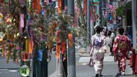 Pengunjung mengenakan kimono saat mengikuti The Star Festival di Haratsuka,Tokyo, Jumat (7/7).  Dalam festival ini mereka menuliskan keinginan dalam potongan kertas berwarna digantungkan pada cabang bambu di sekitar rumah mereka. (AP/Eugene Hoshiko)